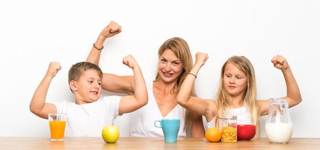 Moeder met haar twee kinderen die ontbijt hebben en overwinningsgebaar maken