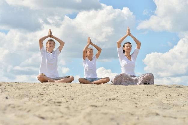 Moeder met haar zonen die op een zand zitten en yoga doen