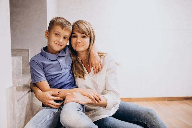 Moeder met haar zoon die samen op vloer zitten