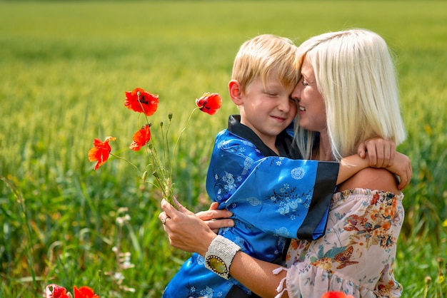 Moeder met haar zoon in een prachtige weide. de jongen omhelst zijn moeder stevig en liefdevol
