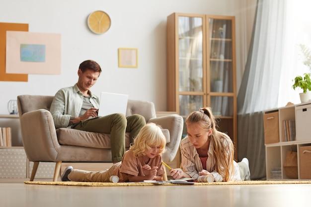 Moeder met haar zoon liggend op de vloer en tekenen terwijl hun vader bezig met laptop zittend op de bank in de woonkamer