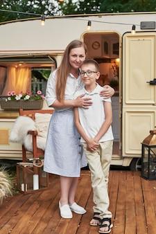 Moeder met haar zoon op vakantie in de zomer in de buurt van het huis op wielen
