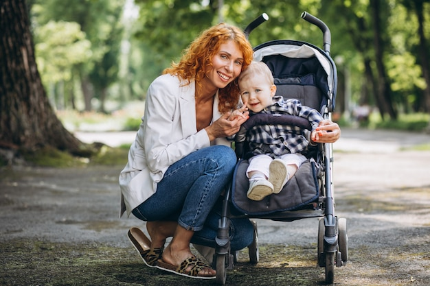 Moeder met haar zoontje in een kinderwagen in het park