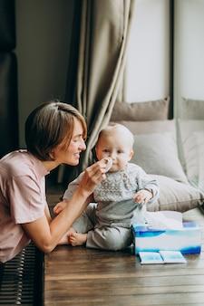 Moeder met haar zoontje met servetten voor loopneus