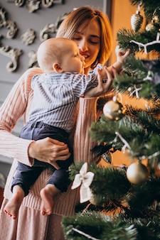 Moeder met haar zoontje versieren kerstboom met speelgoed