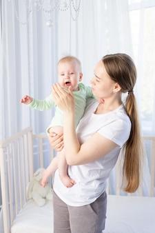 Moeder met huilende baby in haar armen bij de wieg in de slaapkamer, moeder probeert de baby te kalmeren
