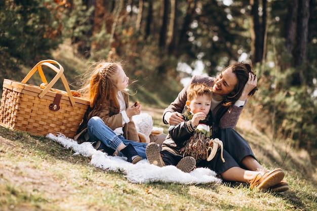 Moeder met jonge geitjes die picknick in het bos hebben