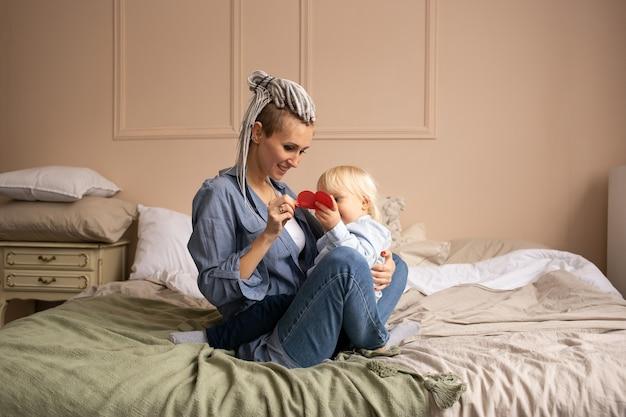 Moeder met jongenszoon thuis op bed. gelukkige familie plezier thuis