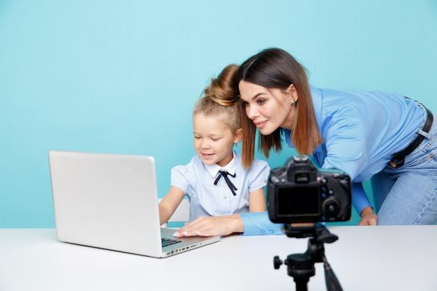 Moeder met kind blogger infront van camera video-opname zitten aan de tafel in de blauwe studio.
