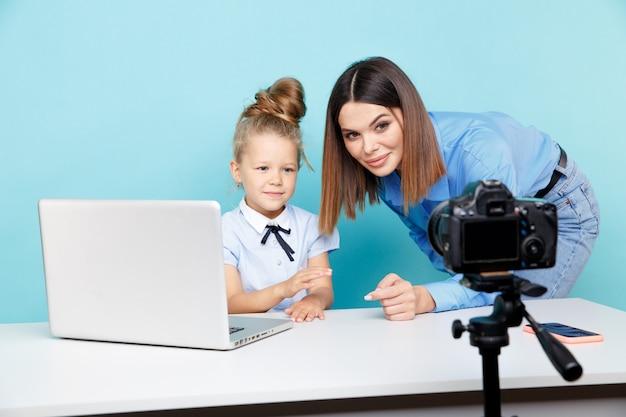 Moeder met kind blogger voor camera-opname video zitten aan de tafel in de blauwe studio