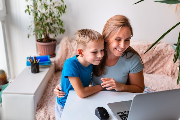 Moeder met kind communiceert online met familieleden via videoconferenties op laptop vanuit huis tijdens quarantaine. communicatieconcept op afstand tijdens een pandemie van het coronavirus