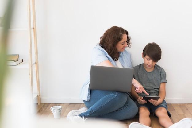 Moeder met kind dat aan laptop werkt