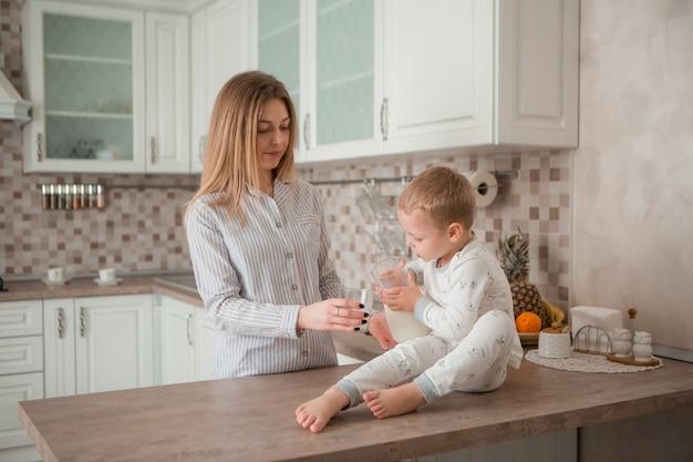 Moeder met kind dat ontbijt in de keuken heeft