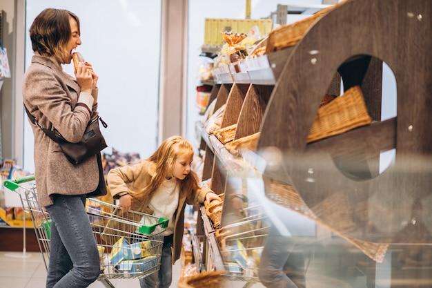 Moeder met kind die brood kiezen bij een kruidenierswinkelopslag