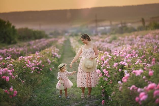 Moeder met kind in een natuurlijk veld met wilde rozen