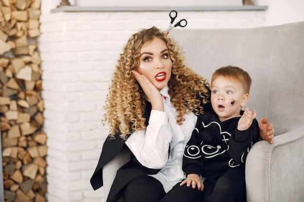 Moeder met kind in kostuums en make-up. familie bereidt zich voor op de viering van halloween.