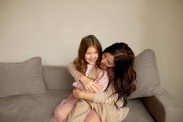 Moeder met kind plezier thuis tijd samen doorbrengen. glimlachende jonge vrouw die gelukkige dochter omhelst Premium Foto