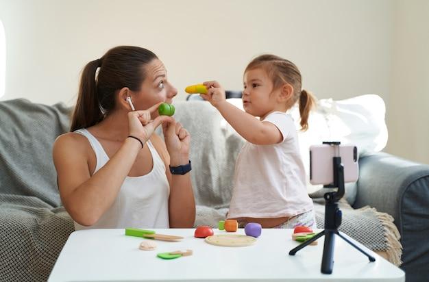 Moeder met kind streaming online video van houten speelgoed uitpakken.