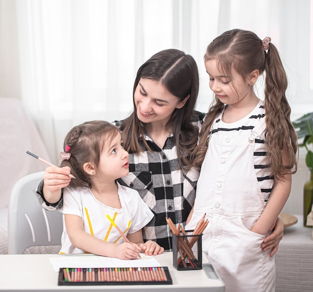 Moeder met kinderen aan de tafel zitten en huiswerk maken. het kind leert thuis. thuisonderwijs. ruimte voor tekst.