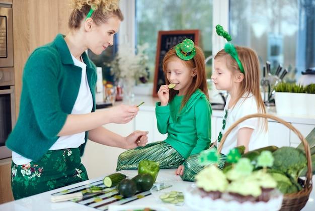 Moeder met kinderen die bij keuken koken