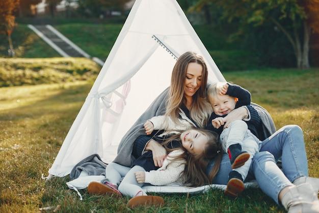 Moeder met kinderen die in een de zomerpark spelen
