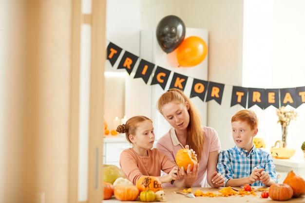 Moeder met kinderen die voor halloween voorbereidingen treffen