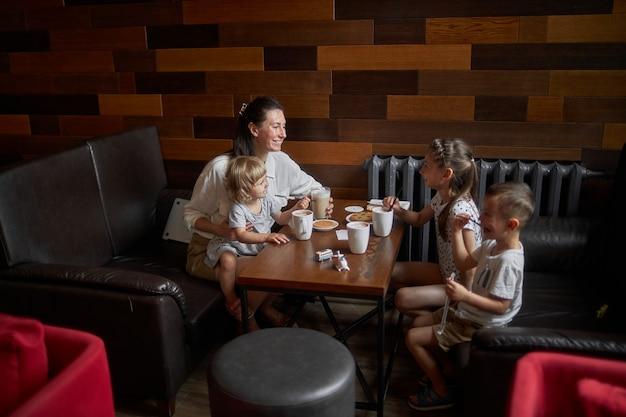 Moeder met kinderen die warme chocolademelk en latte drinken in een plaatselijke coffeeshop. ze glimlachen en hebben plezier. moederschap concept