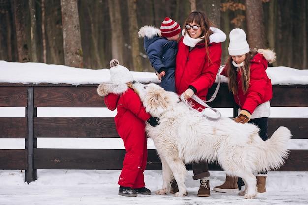 Moeder met kinderen en hond buiten spelen in de winter