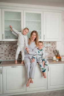 Moeder met kinderen in de keuken