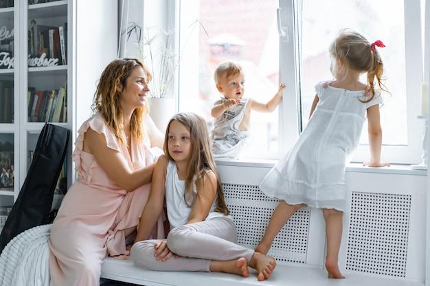 Moeder met kinderen in een huiselijke sfeer. kinderen bij het raam