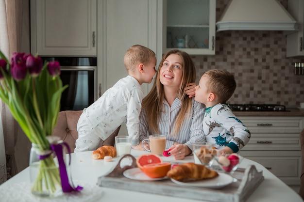 Moeder met kinderen ontbijten in de keuken