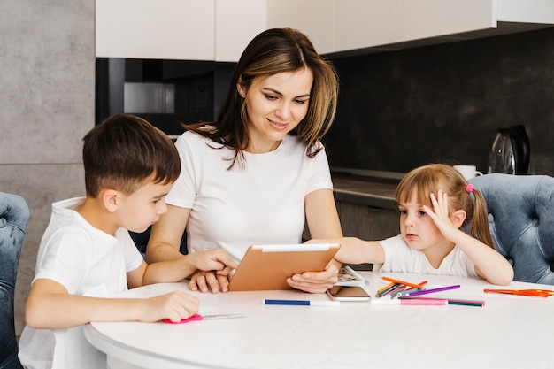 Moeder met kinderen thuis leren van digitale tablet
