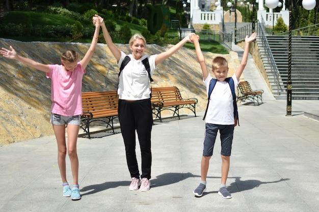 Moeder met kinderen wandelen in het park, gelukkige familie