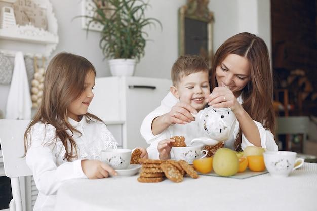 Moeder met kinderen zitten in een keuken en eten