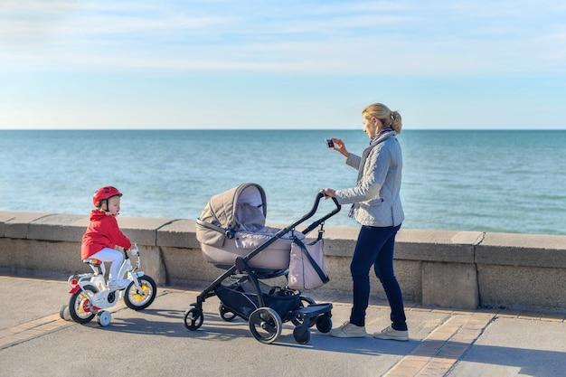 Moeder met kinderwagen en dochter op een fiets lopen samen op het strand