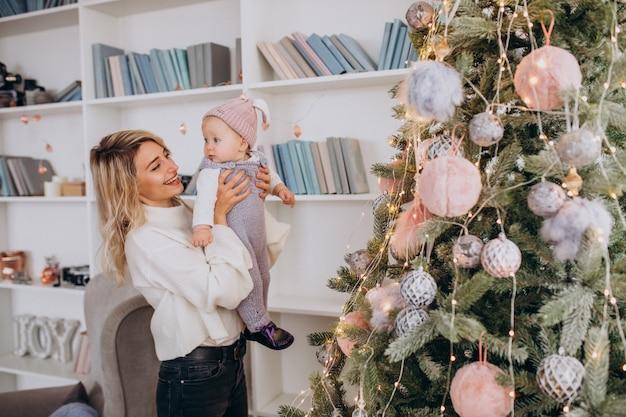 Moeder met kleine dochter bij de kerstboom