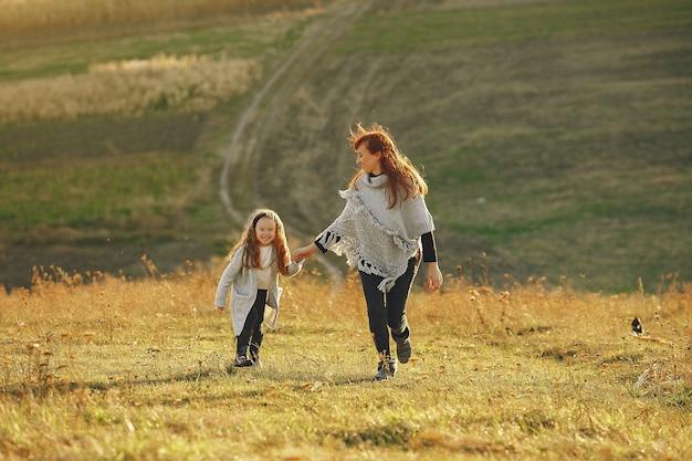 Moeder met kleine dochter die op een de herfstgebied speelt
