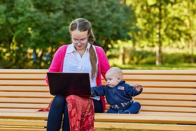 Moeder met kleine jongen maakt werken op afstand met laptop buitenshuis