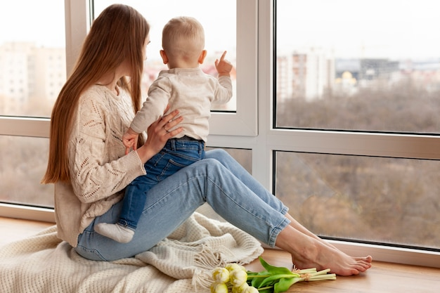 Moeder met kleine jongen op zoek op venster