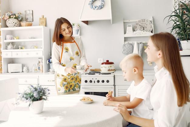 Moeder met kleine kinderen die thee thuis drinken