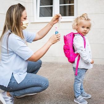 Moeder met medisch masker handdesinfecterend middel aanbrengend kind rugzak
