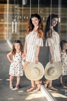 Moeder met meisje in een jurk en hoeden op het terras