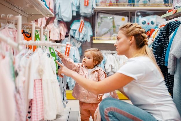 Moeder met meisje kleren kiezen in kinderwinkel