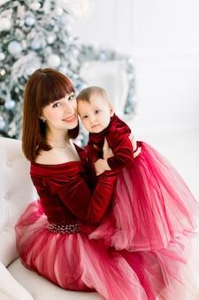 Moeder met meisje, zittend op een stoel op de achtergrond van de kerstboom