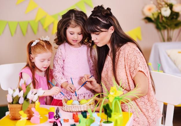Moeder met meisjesdochters die voor de viering van pasen voorbereidingen treffen en eieren kleuren die bij de lijst aangaande de oppervlakte van het pasen-decor zitten