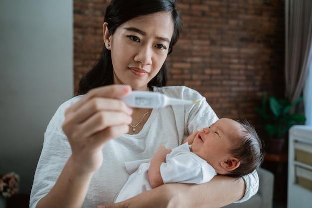 Moeder met pasgeboren baby en thermometer
