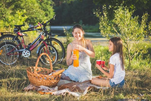 Moeder met picknick aan de rivier met dochter. moeder giet sinaasappelsap in de beker van de dochter
