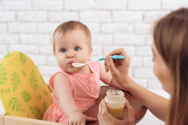 Moeder met puree en lepel die kleine baby voedt
