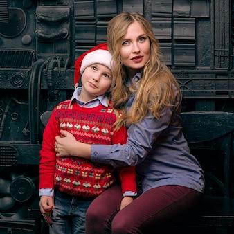 Moeder met santa zoon in industriële fotostudio
