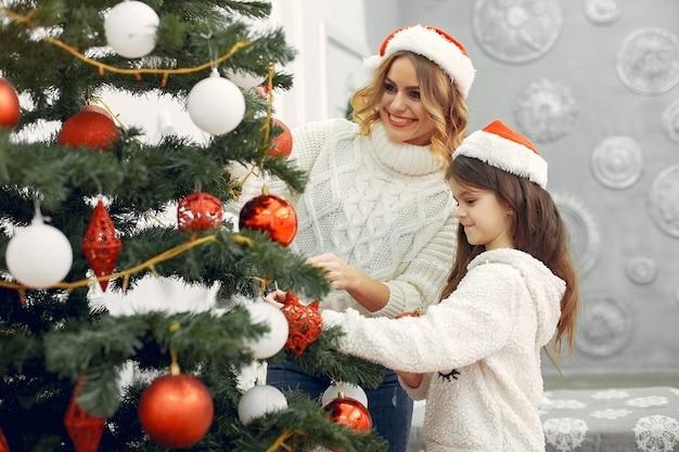 Moeder met schattige dochter die zich dichtbij kerstmisboom bevindt